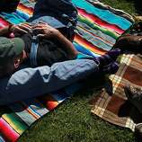 Ron Thompson, center, lounges on Marcia Gill, left, as they wait for the first band to start during the first day of the Hardly Strictly Bluegrass festival in Golden Gate Park October 4, 2013 in San Francisco, Calif.