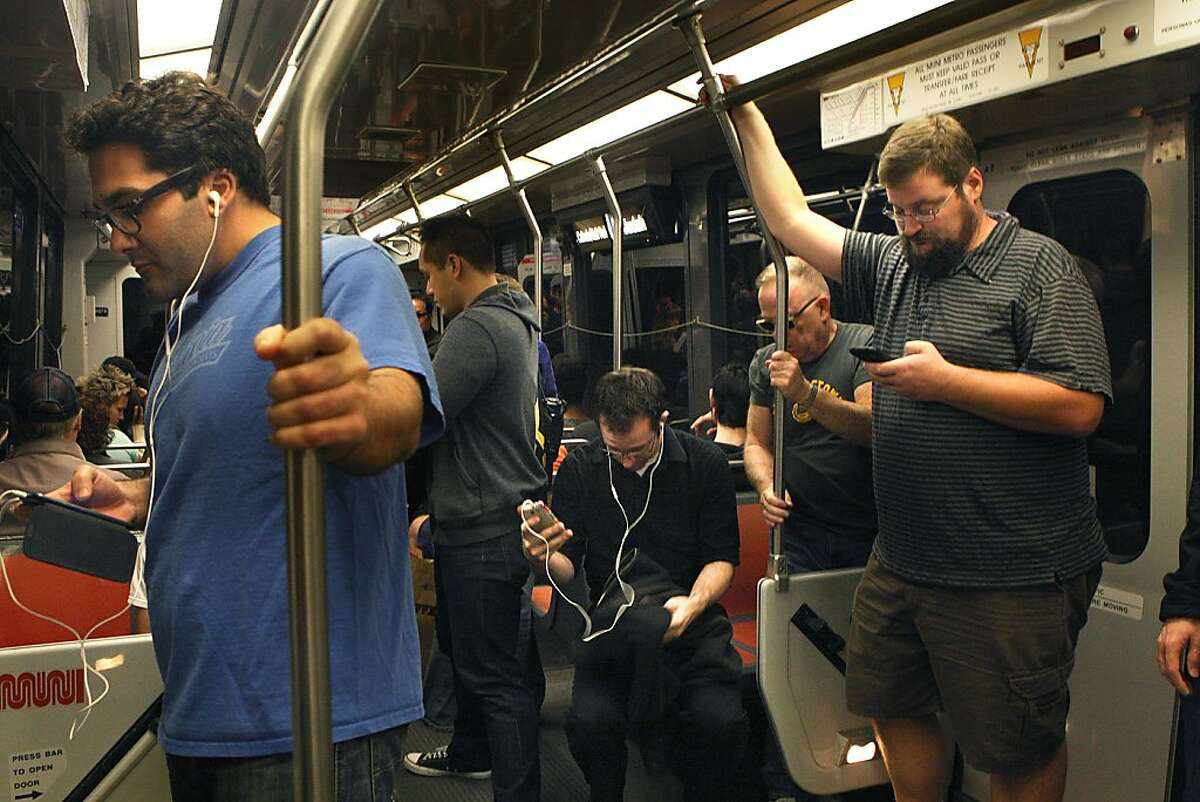 Passengers including Brandon Long (right) on his cell phone while going to work on a Muni train stopping at Powell Street station in San Francisco, California, on Friday, October 4, 2013.