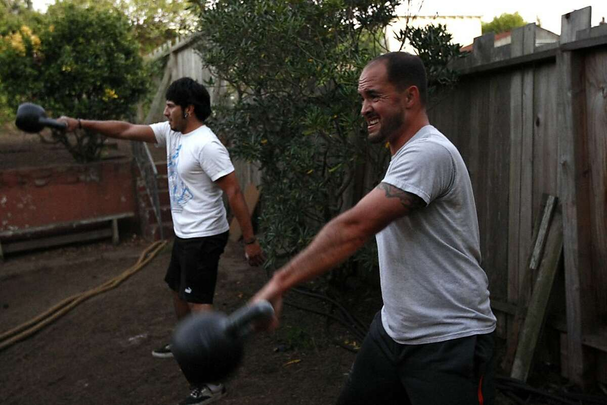 Marine Corps Sgt. and Iraq War veteran Kevin Miller, right, works out with a kettlebell in his backyard with his friend Ash Salcido in San Francisco, California Thursday October 3, 2013. AmeriCorps Vista employee at Swords to Plowshares and Iraq war veteran Kevin Miller, who teeters on the brink of poverty, will have his federally funded paycheck withheld indefinitely due to the government shutdown.