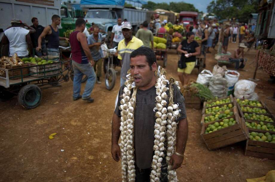 Cuba: Farmer Asley Cruz, 35, wears a string of garlic on his shoulders as he yells prices at the 114th Street Market on the outskirts of Havana, Cuba. The market's bustle is a result of economic reforms begun in 2010 by President Raul Castro, which includes relaxing rules on private farming. In another reform, Cuban authorities recently authorized small farmers to also sell directly to hotels and tourist centers beginning this month. Photo: Ramon Espinosa, Associated Press