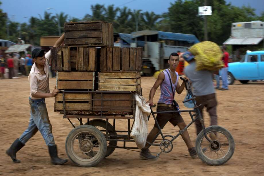 Cuba: Young men men push a tricycle loaded with empty boxes they use to transport produce at the 114th Street Market on the outskirts of Havana, Cuba. The open-air bazaar has become a key hub for getting farm products to people in the capital. Photo: Ramon Espinosa, Associated Press
