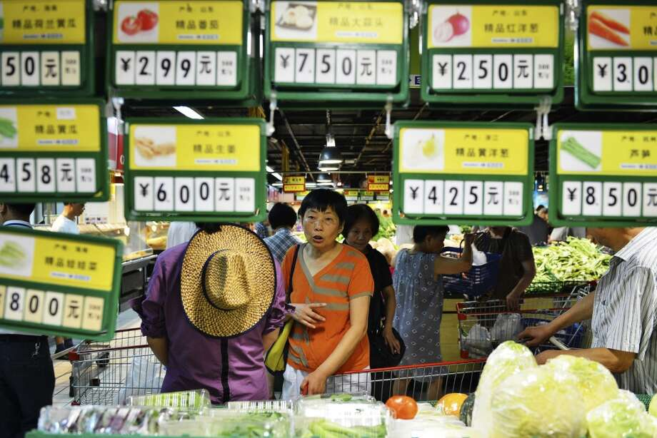 China: A shopper walks past price tags for vegetables at a supermarket in Hangzhou in eastern China's Zhejiang province. Photo: Associated Press