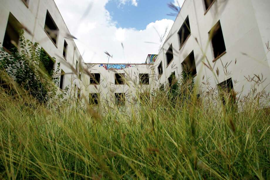 The former Schlumberger building is overgrown but developers plan to renovate the art deco-style building into office and retail space. Photo: Cody Duty, Staff / © 2013 Houston Chronicle