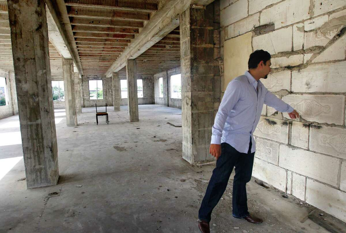 Apurva Sanghavi touches an original portion of the former Schlumberger building at the corner or Leeland and Delano Streets, Wednesday, Oct. 2, 2013, in Houston. Gaurav Khandelwal and Apurva Sanghavi plan to redevelop the building in the East End. (Cody Duty / Houston Chronicle)