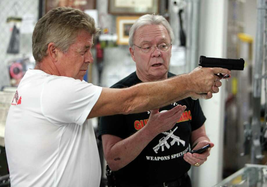 Dave Odlin checks out a handgun as Houston gun dealer Jim Pruett points out the gun's features. Odlin ended up purchasing a Springfield semi-automatic. Photo: Mayra Beltran, Staff / © 2013 Houston Chronicle