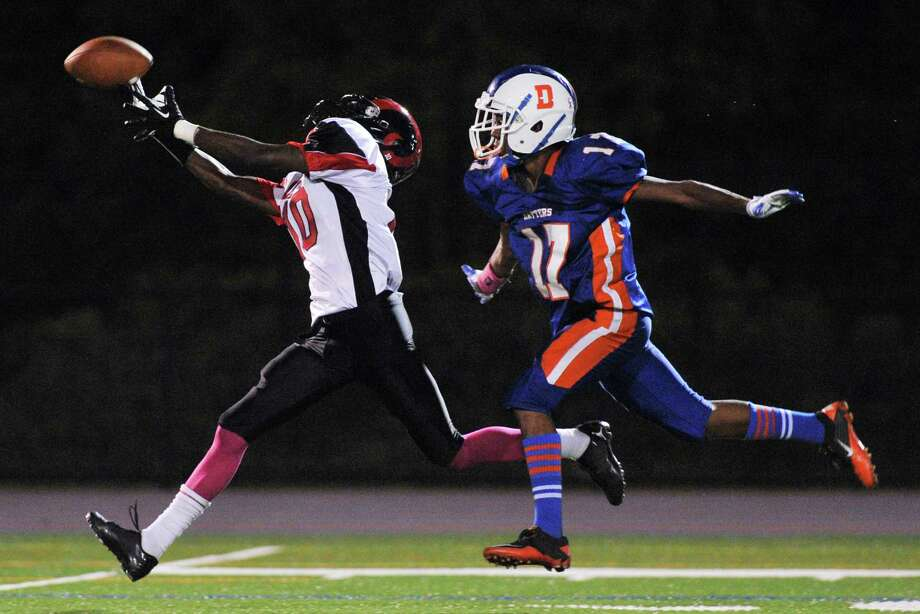 Bridgeport Central receiver Jelani Green reaches out for the ball as Danbury's Matt Andrew defends in the FCIAC high school football game between Danbury and Bridgeport Central at Danbury High School in Danbury, Conn. on Friday, Oct. 4, 2013. Photo: Tyler Sizemore / The News-Times