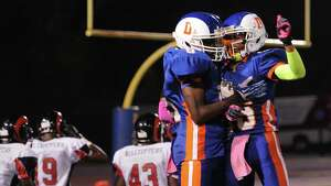 Danbury's Pierre Moudourou, left, celebrates his touchdown with teammate Tysheen McCrea in the FCIAC high school football game between Danbury and Bridgeport Central at Danbury High School in Danbury, Conn. on Friday, Oct. 4, 2013.