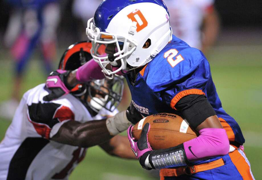 Danbury's Elijah Duffy stiff arms a defender in the FCIAC high school football game between Danbury and Bridgeport Central at Danbury High School in Danbury, Conn. on Friday, Oct. 4, 2013. Photo: Tyler Sizemore / The News-Times