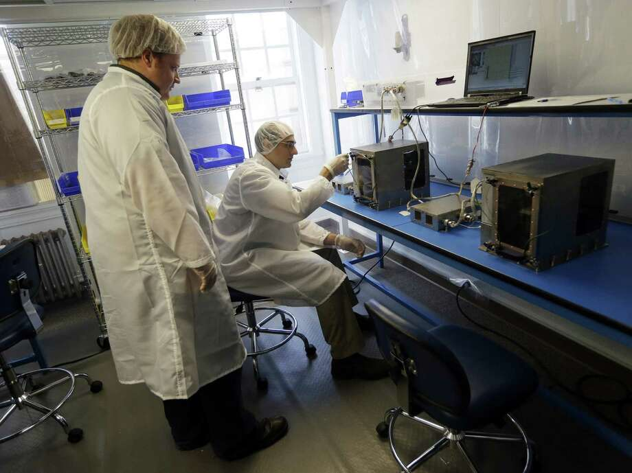 Project manager Matthew Napoli (left) and director of research and development Michael Snyder test a 3-D printer that eventually will be used in space at Made in Space in Mountain View, Calif. Photo: Photo By Marcio Jose Sanchez / Associated Press