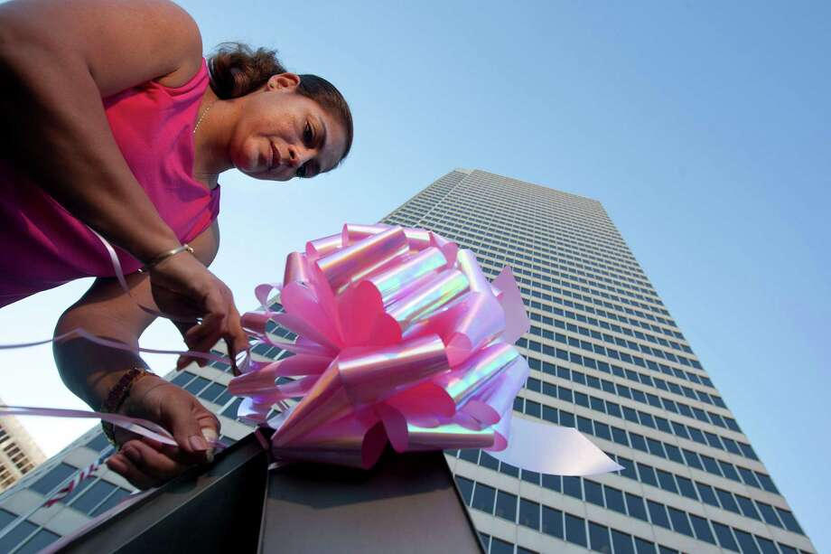 Rosie Villegas places pink ribbons outside of America Tower along Allen Parkway at Waugh as a group decorated signs and trees along the race route for the Susan G. Komen Race for the Cure Friday, Oct. 4, 2013, in Houston. The race route will run down the inbound and outbound lanes of Allen Parkway Saturday. The Survivor Celebration and Sponsor Expo area will still take place in Downtown Houston. Day of race registration begins at 6:00a.m. followed by the opening ceremonies at 7:45 a.m. for more information visit http://www.komen-houston.org. Photo: Johnny Hanson, Houston Chronicle / Houston Chronicle