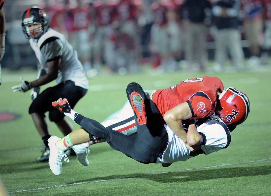 New Canaan's Cole Harris, top, lays-out Fairfield Warde running back Matt Kerigan during the first quarter of the high School football game between New Canaan High School and Fairfield Warde High School at New Canaan, Friday night, Oct. 4, 2013. Photo: Bob Luckey / Greenwich Time