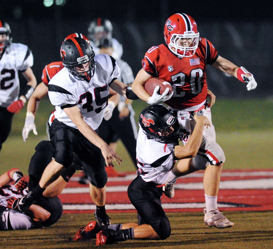 At right, Kyle Smith (# 20) of New Canaan, drags a Fairfield Warde defender along as Fairfield Warde defender Thomas Fitzpatrick (# 35) pursues during the high School football game between New Canaan High School and Fairfield Warde High School at New Canaan, Friday night, Oct. 4, 2013. Photo: Bob Luckey / Greenwich Time