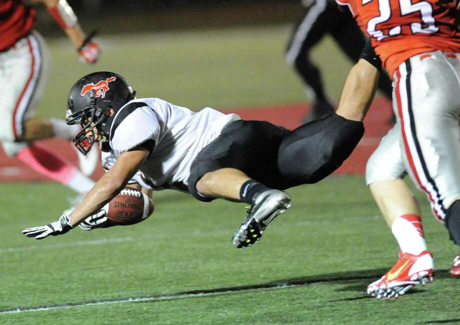 Fairfield Warde running back, Colin Ventura, dives for extra yardage during the high School football game between New Canaan High School and Fairfield Warde High School at New Canaan, Friday night, Oct. 4, 2013. Photo: Bob Luckey / Greenwich Time
