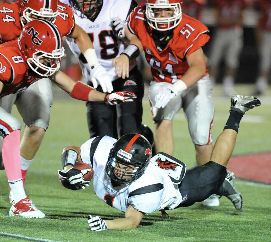Fairfield Warde running back, Colin Ventura, bottom, dives for extra yardage as New Canaan defenders, Robby Paul (# 8), at left, and Beau Santero (# 51), at right, close in during the high School football game between New Canaan High School and Fairfield Warde High School at New Canaan, Friday night, Oct. 4, 2013. Photo: Bob Luckey / Greenwich Time