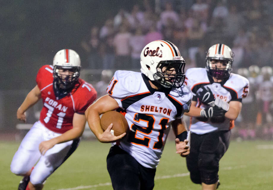 Shelton's Jason Thompson (21) carries the ball during the football game against Foran at Foran High School in Milford on Friday, Oct. 4, 2013. Photo: Amy Mortensen / Connecticut Post Freelance