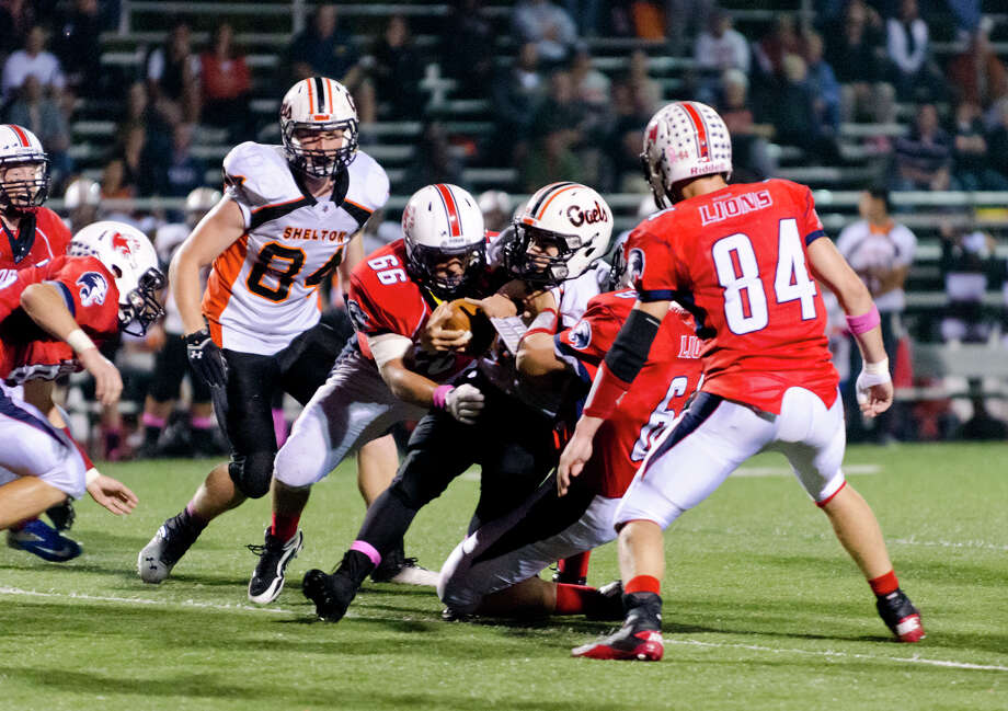 Shelton ball carrier Mark Piccirillo (12) is brought down by Foran's Colin Lydiksen (66) and Michael Howell (64) during the football game at Foran High School in Milford on Friday, Oct. 4, 2013. Photo: Amy Mortensen / Connecticut Post Freelance
