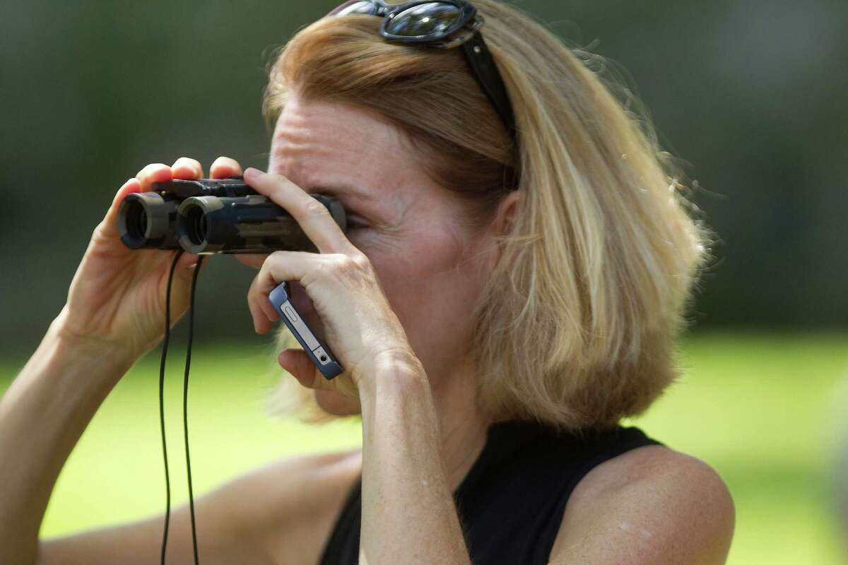 Neighbor, Jill Satterwhite, looks on as FBI agents conducted a search a upscale home on the 2000 block of Albans near Rice Village in the Southampton neighborhood Friday, Oct. 4, 2013, in Houston.