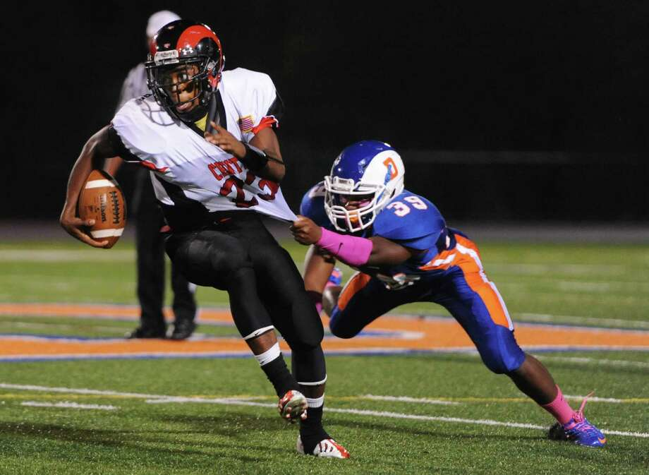 Bridgeport Central's Bilal Muhammad, left, escapes Danbury defender Marlon Black in the FCIAC high school football game between Danbury and Bridgeport Central at Danbury High School in Danbury, Conn. on Friday, Oct. 4, 2013. Photo: Tyler Sizemore / The News-Times