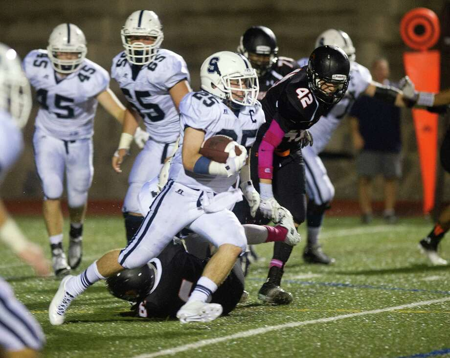 Staples' Patrick Lesch carries the ball during Friday's football game in Stamford, Conn., on October 4, 2013. Photo: Lindsay Perry / Stamford Advocate