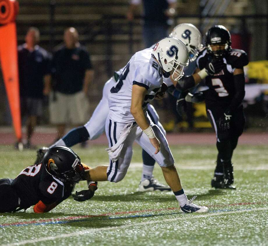 Staples' Jack Greenwald escapes the grasp of Stamford's Rigerson Gelin during Friday's football game in Stamford, Conn., on October 4, 2013. Photo: Lindsay Perry / Stamford Advocate