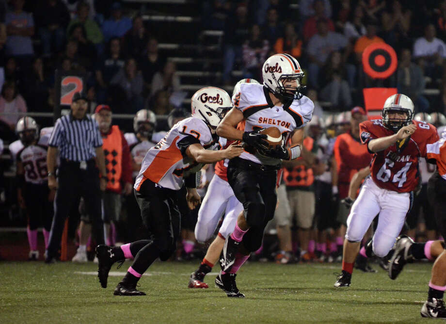 Shelton's Mark Piccirillo (12) hands the ball off to Michael Pingree (14) during the football game against Foran at Foran High School in Milford on Friday, Oct. 4, 2013. Photo: Amy Mortensen / Connecticut Post Freelance
