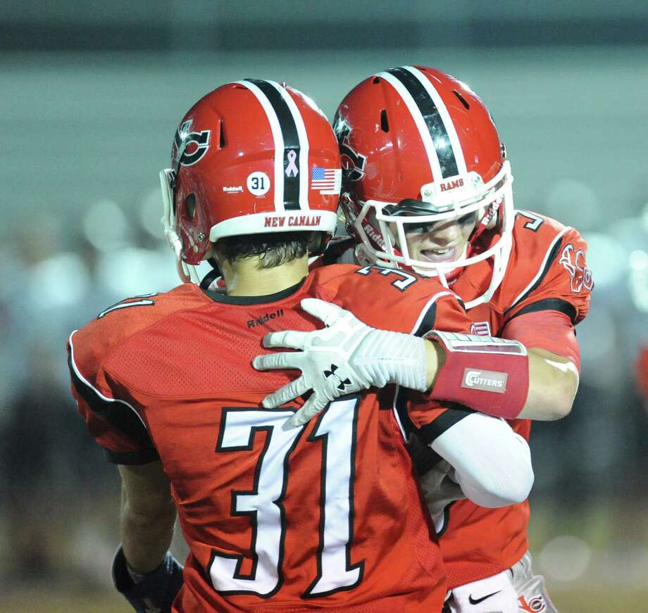 New Canaan's Mike DiCosmo (# 31) and teammate celebrate during the high School football game between New Canaan High School and Fairfield Warde High School at New Canaan, Friday night, Oct. 4, 2013. Photo: Bob Luckey / Greenwich Time