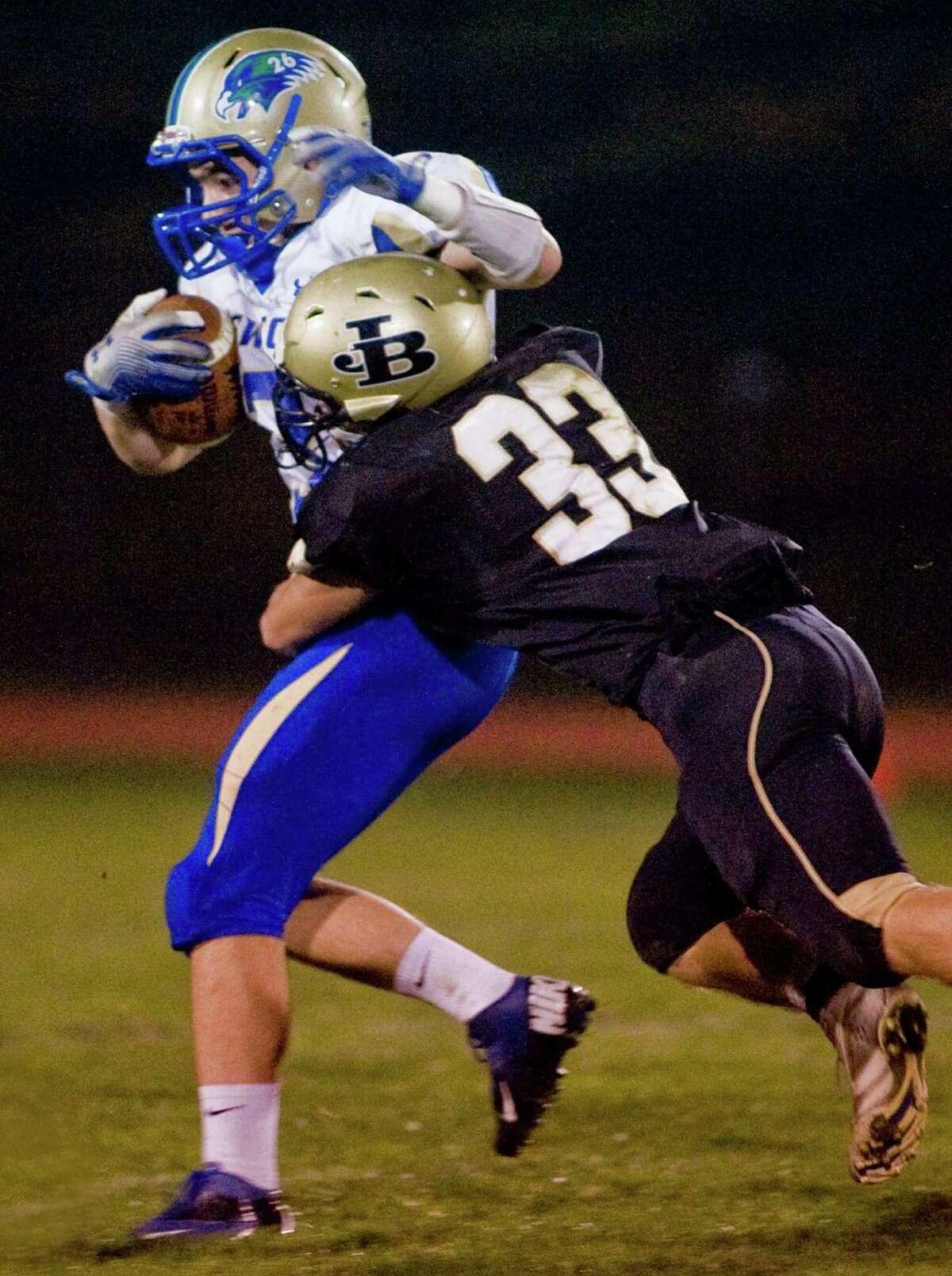 Newtown High School's Troy Frangione is taken down by Joel Barlow's Steve Miller during a game at Joel Barlow High School. Friday, Oct. 4, 2013