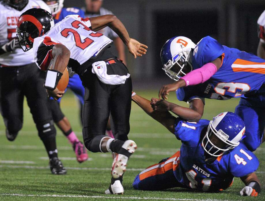 Bridgeport Central's Mykel Morris (23) escapes Danbury defenders Marcus Joyner (41) and Gergory Ashe (33) in the FCIAC high school football game between Danbury and Bridgeport Central at Danbury High School in Danbury, Conn. on Friday, Oct. 4, 2013. Photo: Tyler Sizemore / The News-Times
