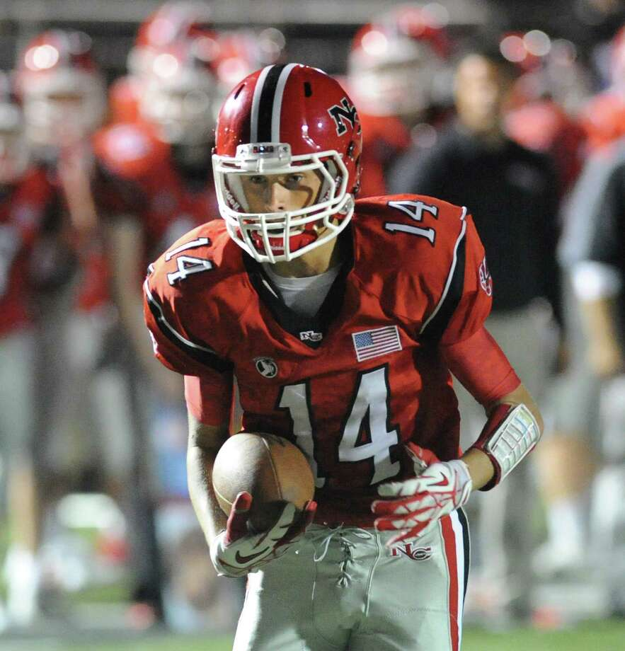 Carson Armstrong (# 14) of New Canaan scores on a pass reception during the second quarter in the high School football game between New Canaan High School and Fairfield Warde High School at New Canaan, Friday night, Oct. 4, 2013. Photo: Bob Luckey / Greenwich Time