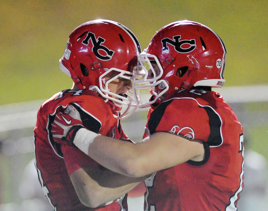 Carson Armstrong (# 14,) left, of New Canaan, celebrates his second quarter touchdown with teammate, Joao Rocha (# 72), during the high School football game between New Canaan High School and Fairfield Warde High School at New Canaan, Friday night, Oct. 4, 2013. Photo: Bob Luckey / Greenwich Time
