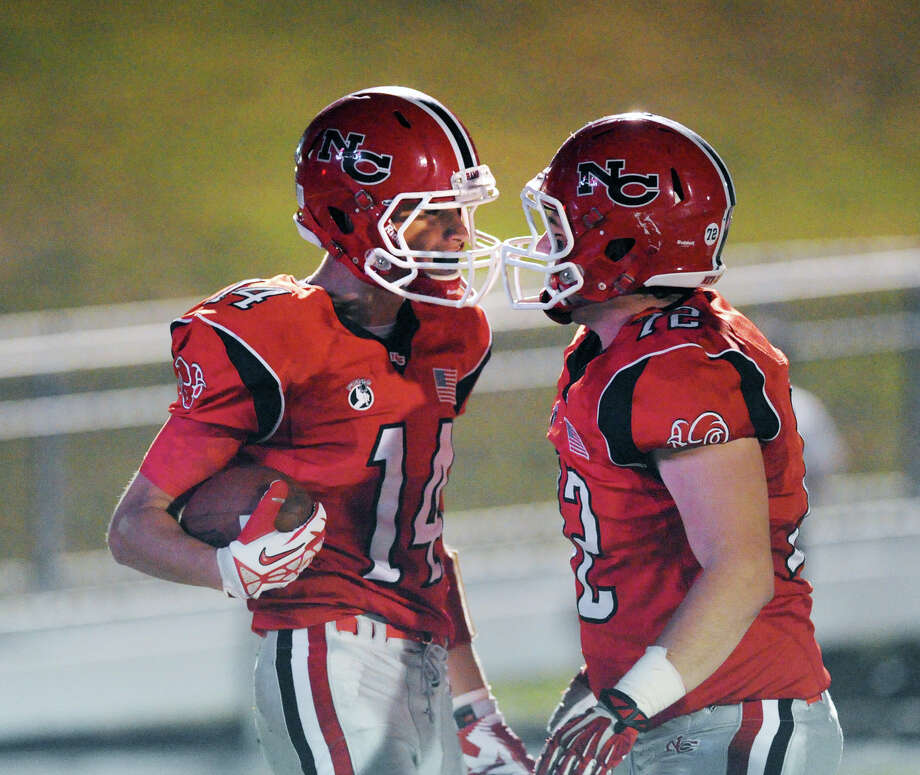 Carson Armstrong (# 14,) left, of New Canaan, celebrates his second quarter touchdown with teammate, Joao Rocha (# 72) during the high School football game between New Canaan High School and Fairfield Warde High School at New Canaan, Friday night, Oct. 4, 2013. Photo: Bob Luckey / Greenwich Time