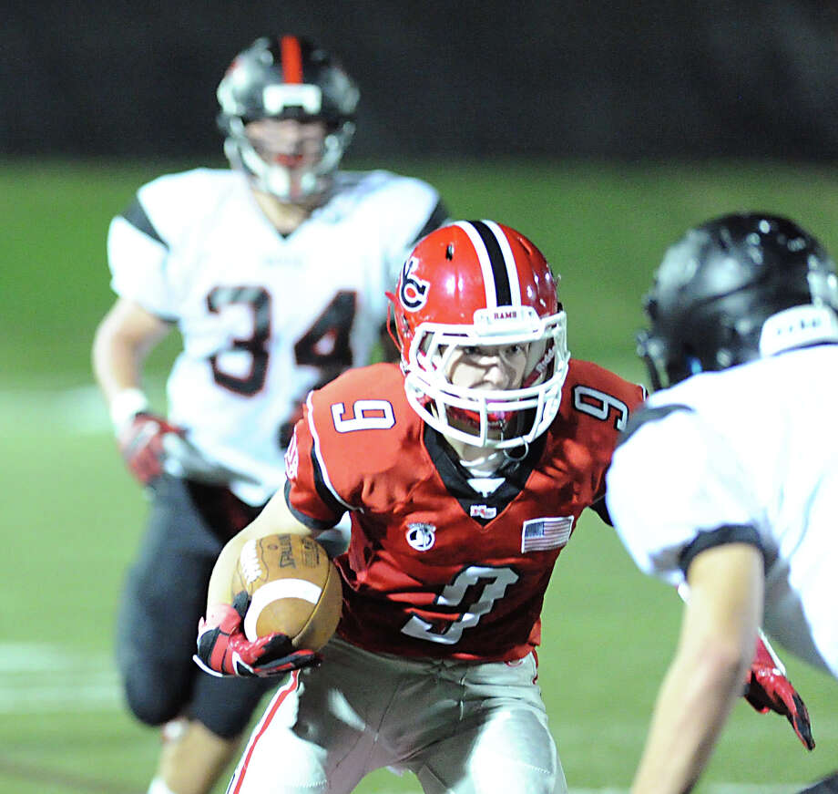 Cole Turpin (# 9) of New Canaan runs the ball during the high School football game between New Canaan High School and Fairfield Warde High School at New Canaan, Friday night, Oct. 4, 2013. Trailing the play is Max Snapper (# 34) of Fairfield Warde High School. Photo: Bob Luckey / Greenwich Time