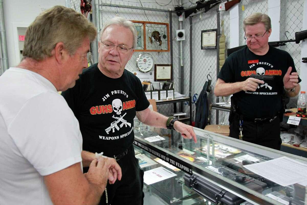 Dave Odlin listens to Jim Pruett, owner of Jim Pruett's Gun's & Ammo store, about gun features on Wednesday, Oct. 2, 2013.