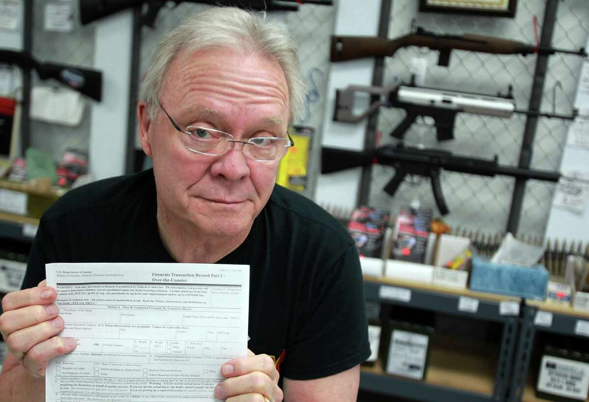 Jim Pruett, owner of Gun's & Ammo, holds the federal form needed to buy a gun, Oct. 2, 2013. Pruett's store closed in 2014.