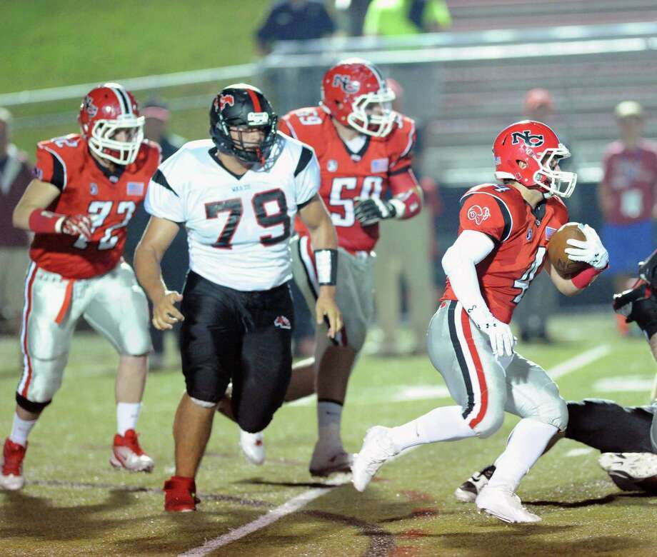 At right, New Canaan's Frank Cognetta (# 4) carries the ball while being pursued by Fairfield Warde's Ahmed Hourani (# 79) during high School football game between New Canaan High School and Fairfield Warde High School at New Canaan, Friday night, Oct. 4, 2013. Photo: Bob Luckey / Greenwich Time