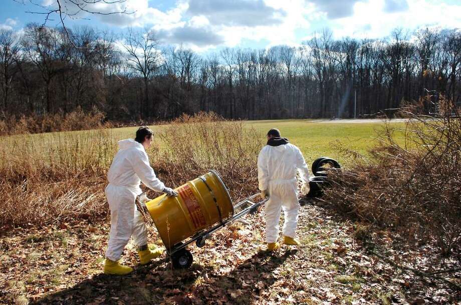 Two workers from Environmental Services, Inc., of South Windsor, CT, neither of whom would give their name, cart away a safety drum which contains an old drum which was discovered on the property of Scofield Magnet Middle School, Tuesday Jan. 26th, 2010. Photo: Bob Luckey / Stamford Advocate