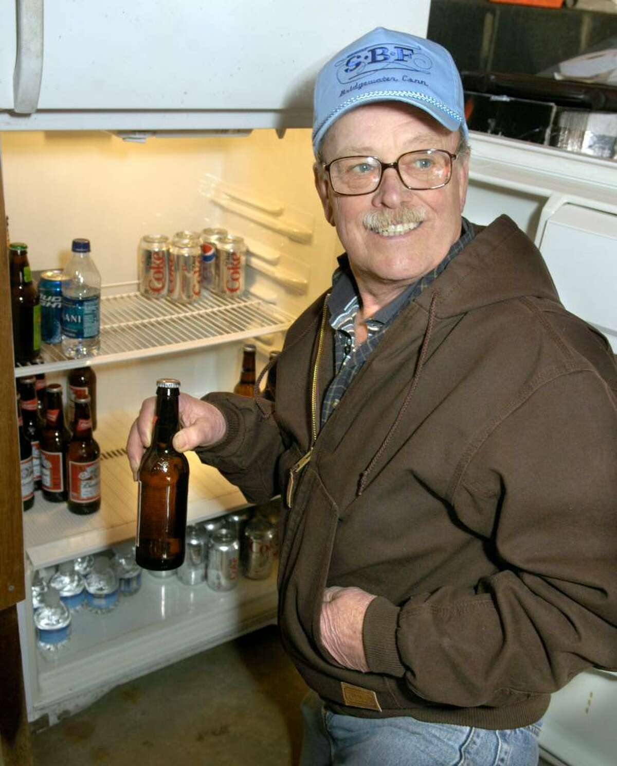 Bridgewater First Selectman Bill Stuart reaches for a beer in a refrigerator that he keeps stocked in his garage Thursday, January 14, 2010.