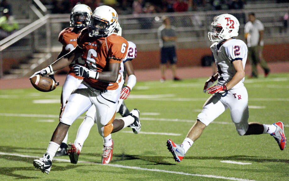 Madison's Dominique Daniels scores a touchdown ahead of Roosevelt's Tyler Tupper during first half action Friday Oct. 4, 2013 at Heroes Stadium. Photo: Edward A. Ornelas, San Antonio Express-News / © 2012 San Antonio Express-News