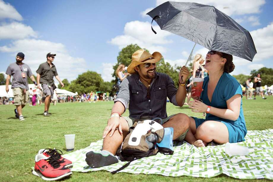 Krys Lambiase and Margret Adams of San Antonio get some shade from the sun during the early hours of the first day of Austin City Limits festival in Austin, Texas, on Friday Oct. 4, 2013. Photo: Erika Rich, Associated Press / Austin American-Statesman