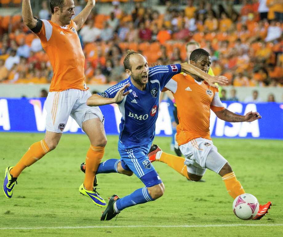 Montreal Impact midfielder Justin Mapp, center, is taken down by Houston Dynamo midfielder Corey Ashe, right, as he gets past midfielder Brad Davis during the first half of an MLS soccer match on Friday, Oct. 4, 2013, at BBVA Compass Stadium in Houston. Photo: Smiley N. Pool, Houston Chronicle / © 2013  Houston Chronicle