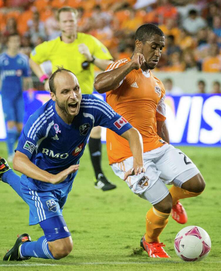 Montreal Impact midfielder Justin Mapp, left, is taken down by Houston Dynamo midfielder Corey Ashe during the first half of an MLS soccer match on Friday, Oct. 4, 2013, at BBVA Compass Stadium in Houston. Photo: Smiley N. Pool, Houston Chronicle / © 2013  Houston Chronicle