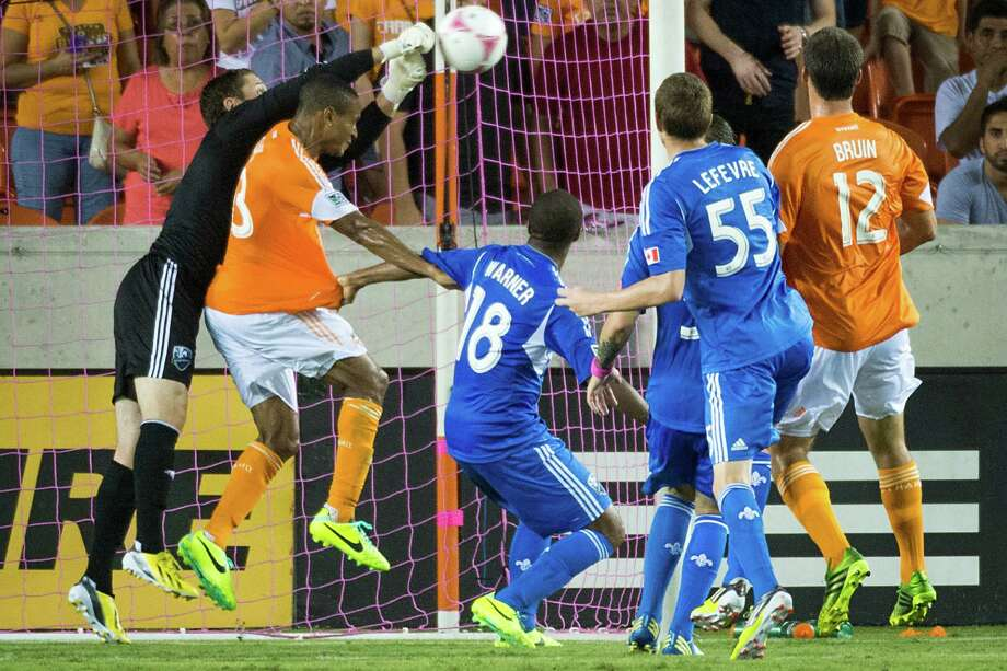 Montreal Impact goalkeeper Troy Perkins punches the ball away from Houston Dynamo midfielder Ricardo Clark (13) during the first half of an MLS soccer match on Friday, Oct. 4, 2013, at BBVA Compass Stadium in Houston. Photo: Smiley N. Pool, Houston Chronicle / © 2013  Houston Chronicle