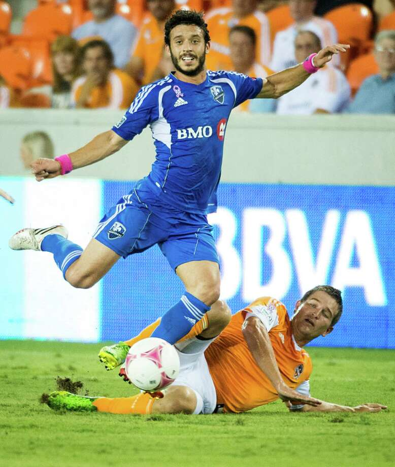 Montreal Impact midfielder Felipe Martins (7) leaps over Houston Dynamo defender Bobby Boswell during the first half of an MLS soccer match on Friday, Oct. 4, 2013, at BBVA Compass Stadium in Houston. Photo: Smiley N. Pool, Houston Chronicle / © 2013  Houston Chronicle