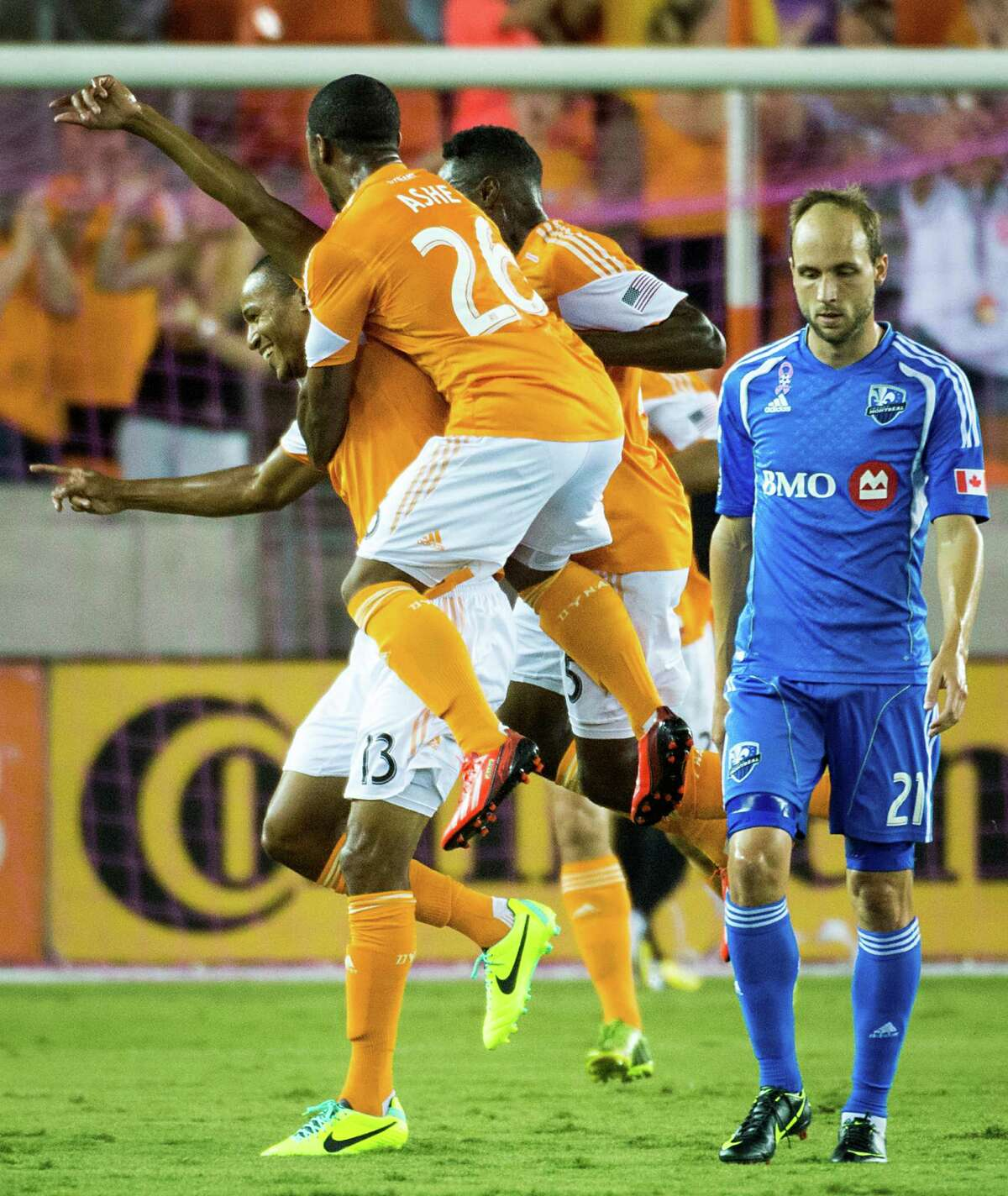 Houston Dynamo midfielder Ricardo Clark (13) celebrates with midfielder Corey Ashe (26) as Montreal Impact midfielder Justin Mapp (21) walks away after Clark scored a goal during the first half of an MLS soccer match on Friday, Oct. 4, 2013, at BBVA Compass Stadium in Houston.