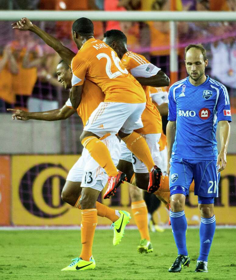 Houston Dynamo midfielder Ricardo Clark (13) celebrates with midfielder Corey Ashe (26) as Montreal Impact midfielder Justin Mapp (21) walks away after Clark scored a goal during the first half of an MLS soccer match on Friday, Oct. 4, 2013, at BBVA Compass Stadium in Houston. Photo: Smiley N. Pool, Houston Chronicle / © 2013  Houston Chronicle