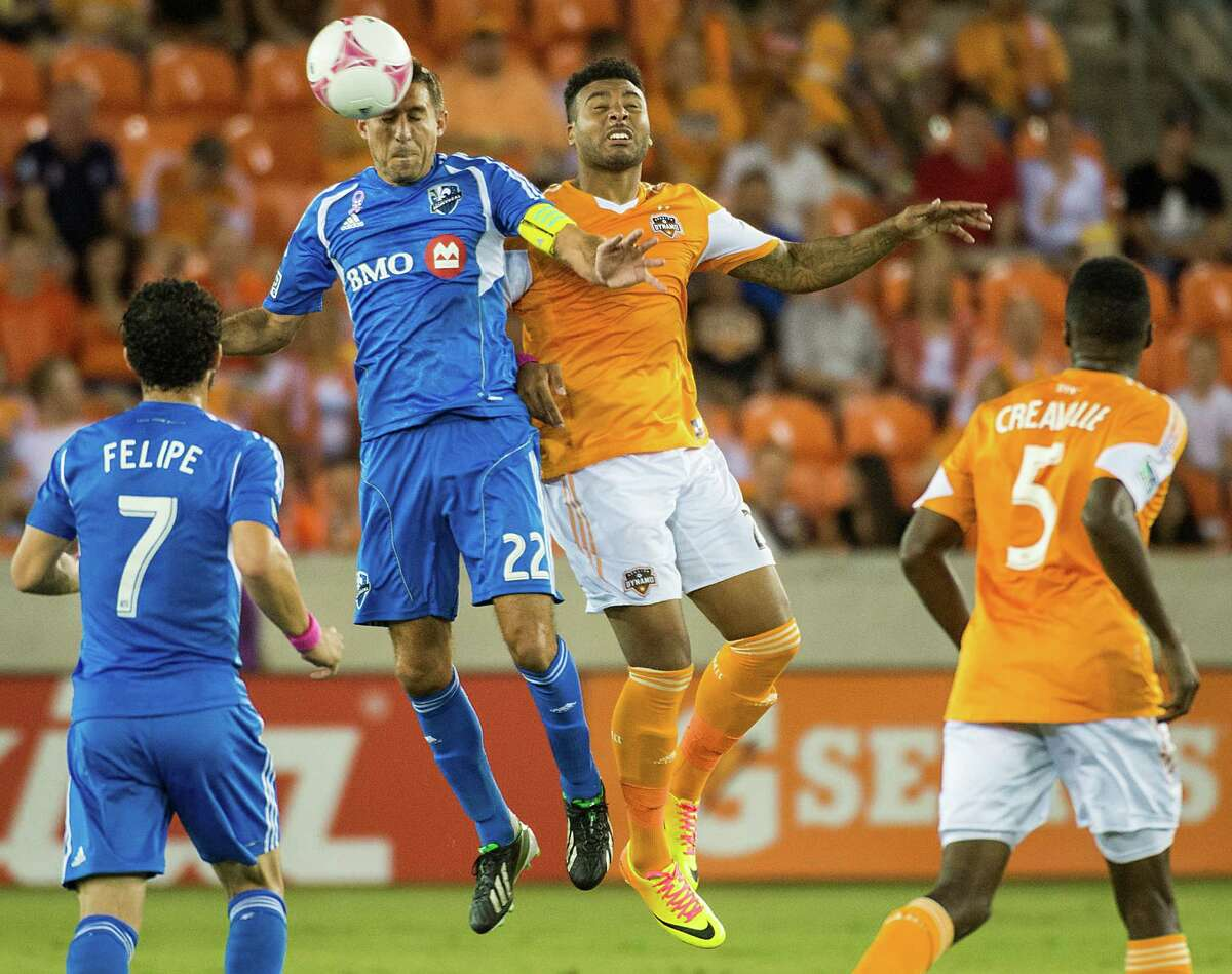 Montreal Impact midfielder Davy Arnaud (22) wins a header from Houston Dynamo midfielder Giles Barnes (23) during the first half of an MLS soccer match on Friday, Oct. 4, 2013, at BBVA Compass Stadium in Houston.
