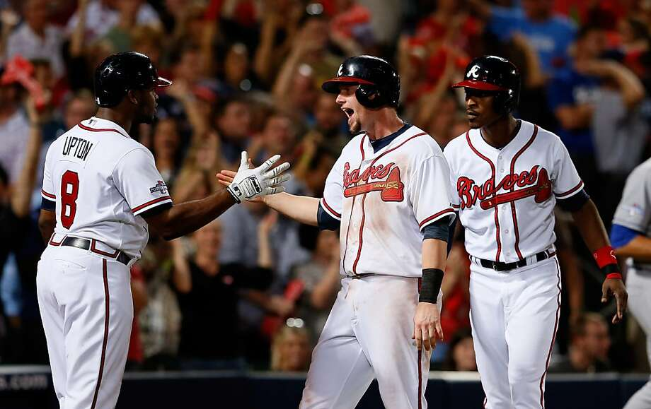 Justin Upton (8) greets Chris Johnson and B.J. Upton at home after they scored on a Jason Heyward single to give the Braves a 4-1 lead over the Dodgers in the bottom of the seventh. Photo: Kevin C. Cox, Getty Images