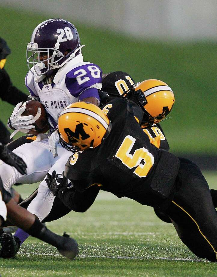 Ridge Point running back Je'Marcus Johnson is tackled by Fort Bend Marshall's Darion Bevel during a high school football game between Ridge Point and Fort Bend Marshall Friday October 4, 2013. (Bob Levey/For The Chronicle) Photo: Bob Levey, Houston Chronicle / ©2013 Bob Levey
