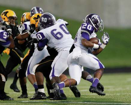 Ridge-Point's KeShawn Ledet runs behind the block of Danny Woodard (60) during a high school football game between Ridge Point and Fort Bend Marshall Friday October 4, 2013. (Bob Levey/For The Chronicle) Photo: Bob Levey, Houston Chronicle / ©2013 Bob Levey