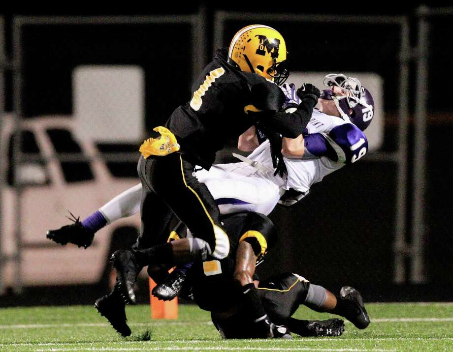 Ridge Point's Jax Bigger (19) completes a pass for a touchdown as he takes a hard hit from Fort Bend Marshall's Jordan Horace during a high school football game between Ridge Point and Fort Bend Marshall Friday October 4, 2013. (Bob Levey/For The Chronicle) Photo: Bob Levey, Houston Chronicle / ©2013 Bob Levey